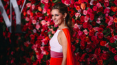 Mean Girls lead Taylor Louderman looks as colorful as the flowers behind her.