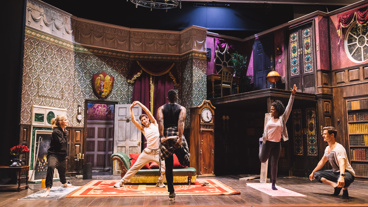 The cast of The Play That Goes Wrong stretches it out before a performance.